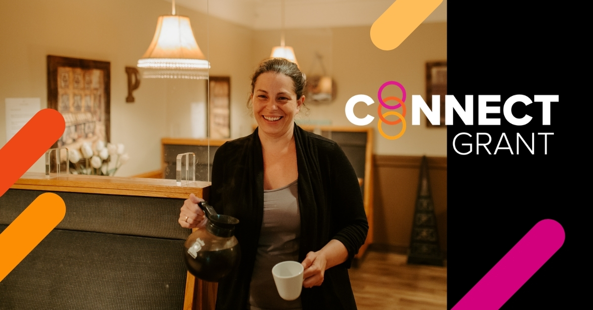 """A smiling woman holds a coffee carafe and a mug in a cafe. The text """"connect grant"""" is on the right."""